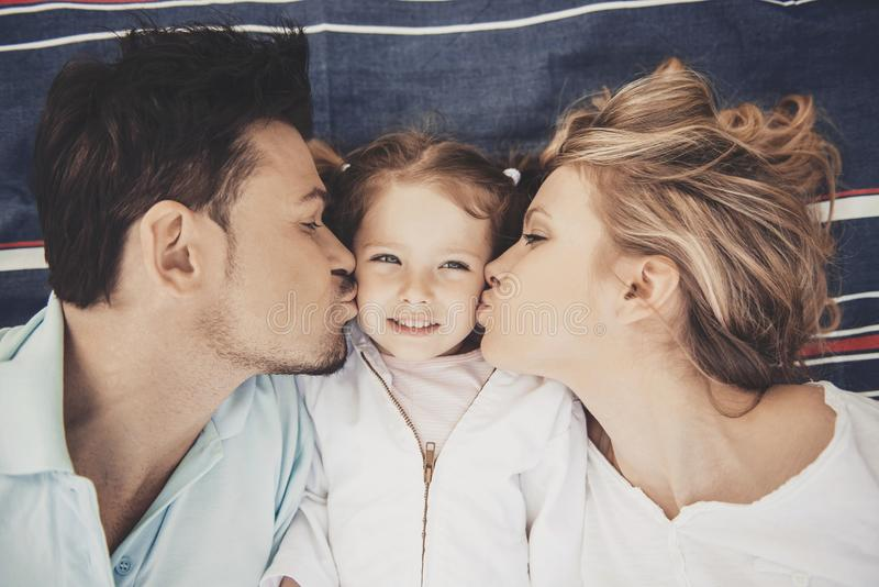 Top view. Mother and Father Kisses Happy Daughter. royalty free stock photo