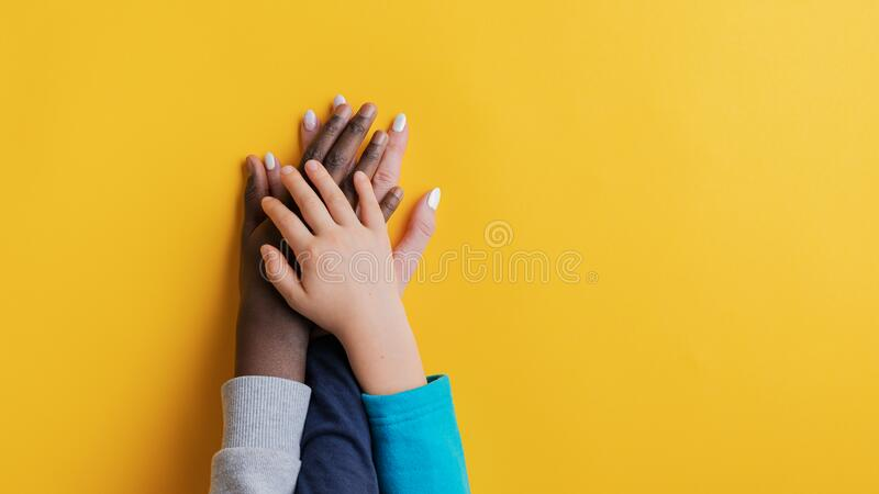 Mother and her two kids, one caucasian one black, stacking their hands royalty free stock photos