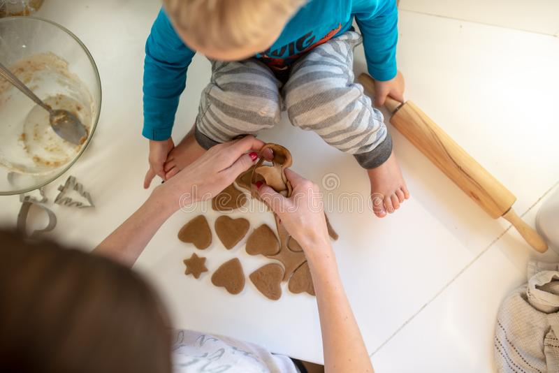 Top view of a mother making heart shaped cookies with her toddler son stock photos