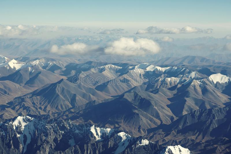 Top view of mountain range layers from airplane window, Tiansan, Xinjiang, China. Top view of Tiansan mountain range from airplane window in clear sunny day royalty free stock photo