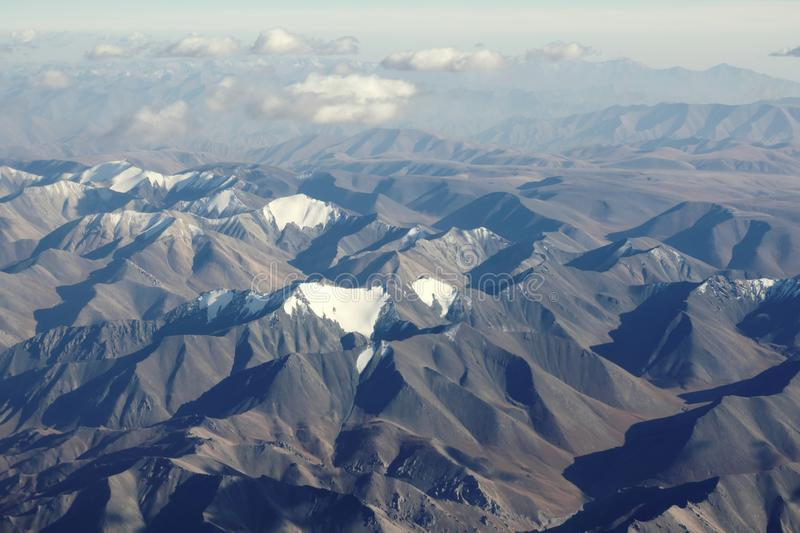 Top view of mountain range layers from airplane window, Tiansan, Xinjiang, China. Top view of Tiansan mountain range from airplane window in clear sunny day stock photos