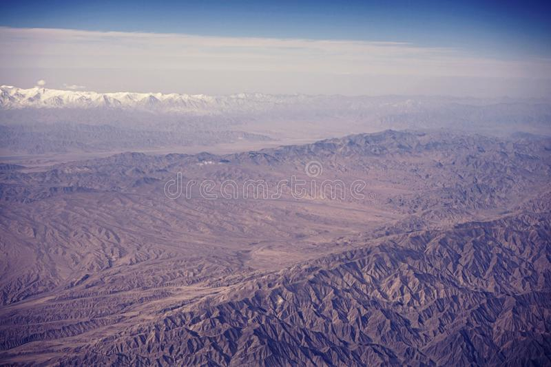 Top view of mountain range layers from airplane window, Tiansan, Xinjiang, China. Top view of mountain range layers from airplane window with cloud and blue sky royalty free stock photos