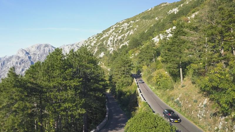 Top view of mountain road traffic. Stock. Traffic on mountain track in summer. Motorcyclist goes to meet adventures on stock images