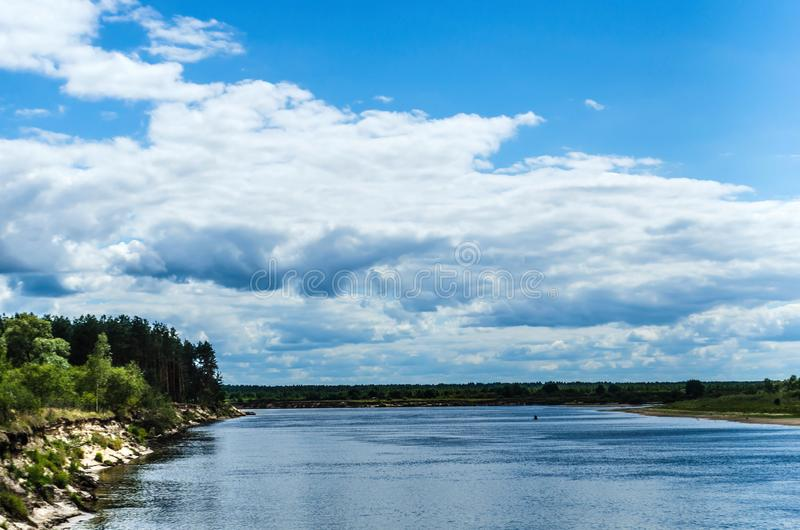 Top view from the mountain to the wide river with a steep rocky coast stock image