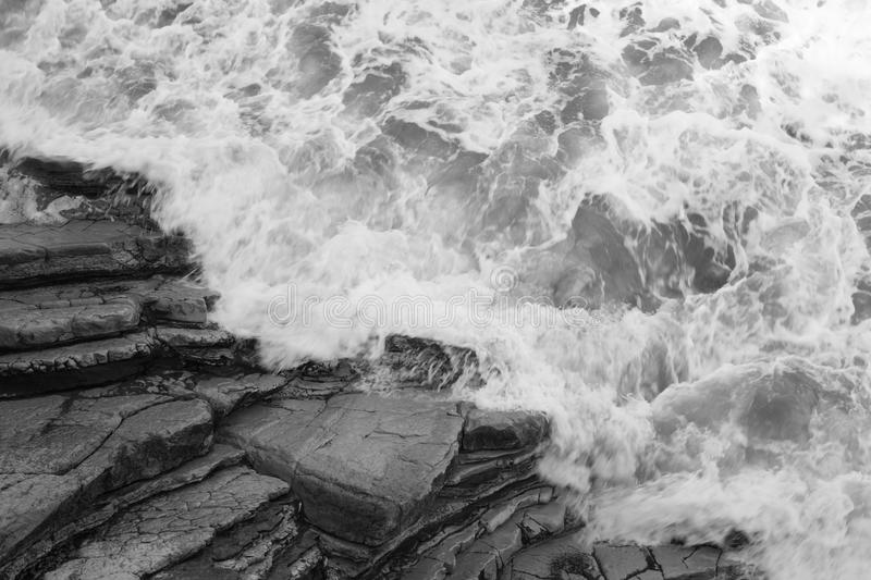 Top view on moving sea water against rocks with waves and foam, texture background pattern in black and white. Top view on moving sea water against rocks with royalty free stock photo