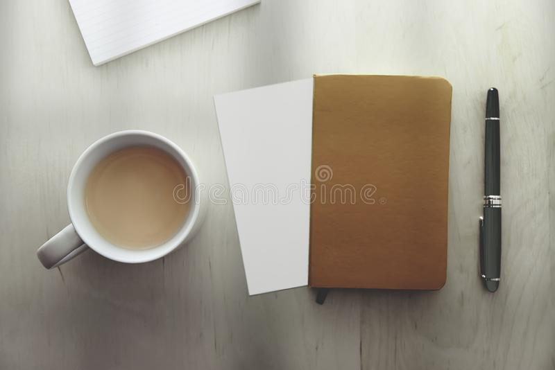 Top view of a mug with coffee, a notebook, a pen and blank paper on a wooden desk table next to a window. Empty copy space stock photography
