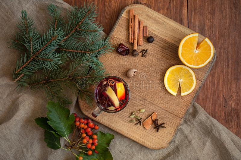 Top view mulled wine with citrus, cinnamon, cardamon and anise spices and fir. Christmas cozy flatlay on wooden rustic royalty free stock photo