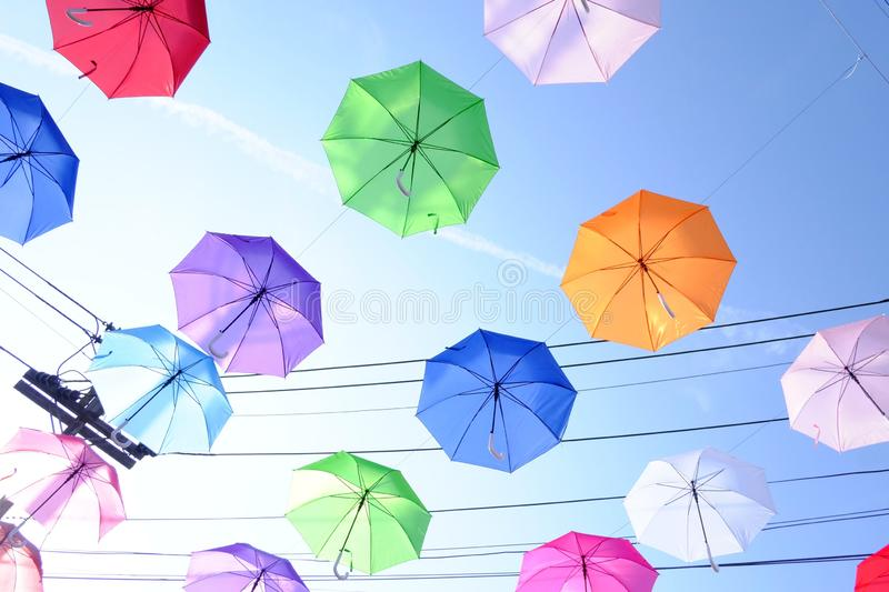 Top view multicolored umbrellas hanging on a wire against blue sky white clouds in bright day and electricity lines background stock photo