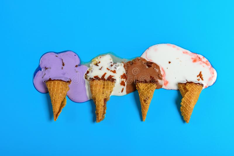 Multiple flavor ice cream cones melted on blue background stock image