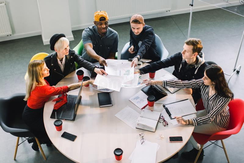 Top view of multiracial young creative people in modern office. Group of young business people are working together with stock photography