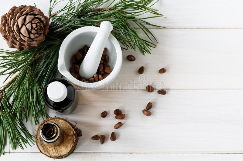 Top view, natural product composition glass bottles with cedar oil, pine nuts, mortar, cedar essential oil stock images