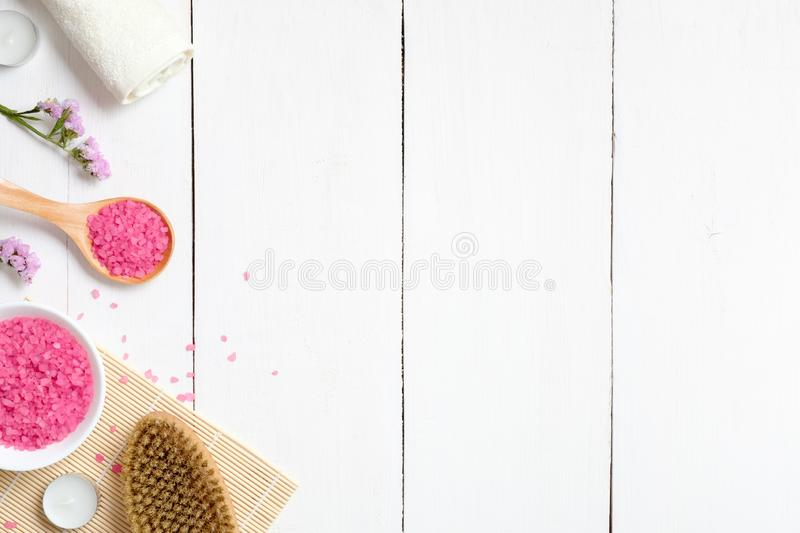 Top view of natural skincare and spa cosmetic products on white wooden table, flat lay. Frame of sea bath salt, massage brush, royalty free stock photo