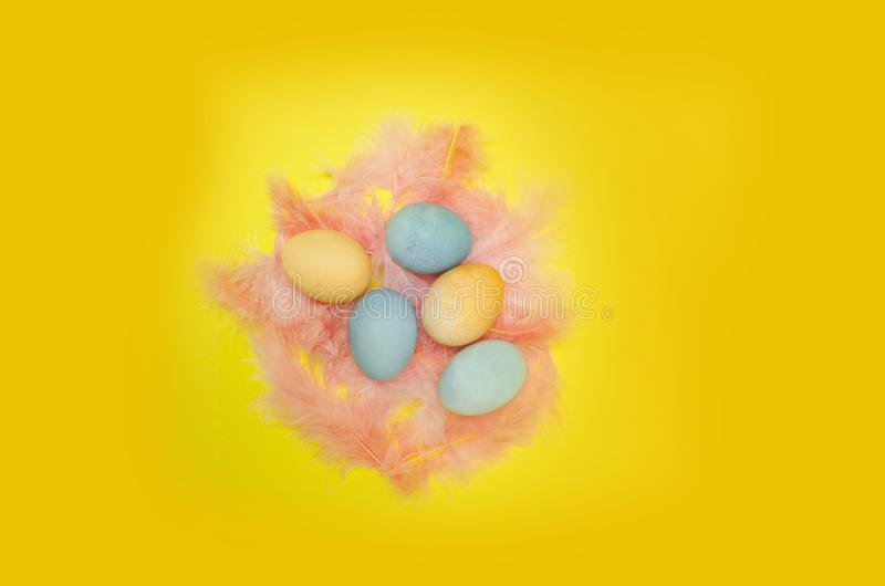 Top view of nest made with colorful feathers, painted eggs on yellow background stock photos