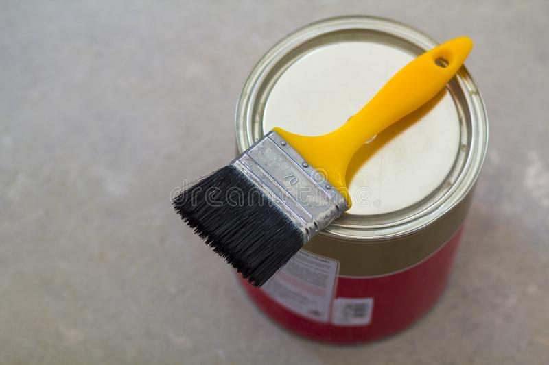 Top view of new shiny clean sealed tin full of red paint and painting brush on it, on white. Tools, materials, building a royalty free stock photography