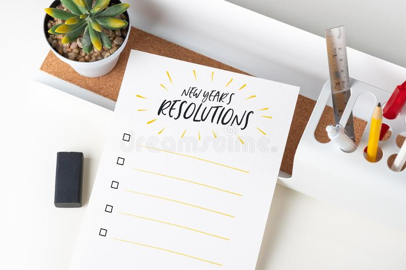 Top view new year`s resolutions checklist on white paper note on modern office stationery on white table.pencil, notepad,ruler,pe. N and pencil box with plant royalty free stock photo