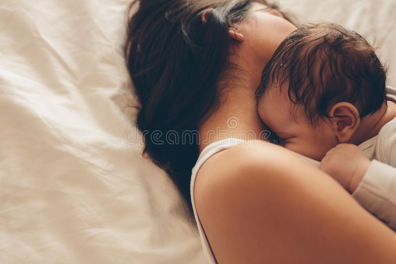 Newborn baby boy sleeping with his mother on bed. Top view of newborn baby boy sleeping with his mother on bed. Mother and son sleeping together at home royalty free stock images