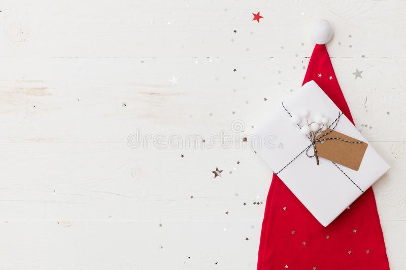 Top view on nice Christmas gift wrapped in white gift paper, Christmas decorations in Santa`s hat on wooden background. Top view on nice Christmas gift wrapped royalty free stock photography