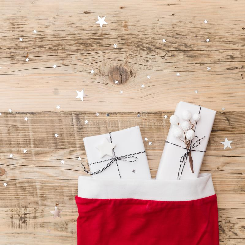 Top view on nice Christmas gifts wrapped in white gift paper, Christmas decorations in Santa`s hat on wooden background. Top view on nice Christmas gifts wrapped royalty free stock photos