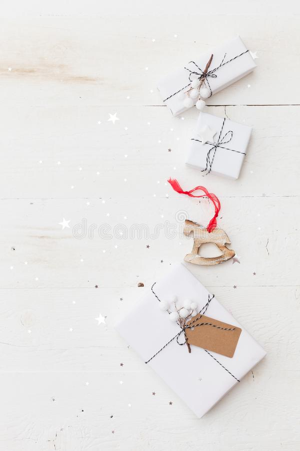 Top view on nice Christmas gifts wrapped in white gift paper, Christmas decorations on white wooden background. Top view on nice Christmas gifts wrapped in white royalty free stock image