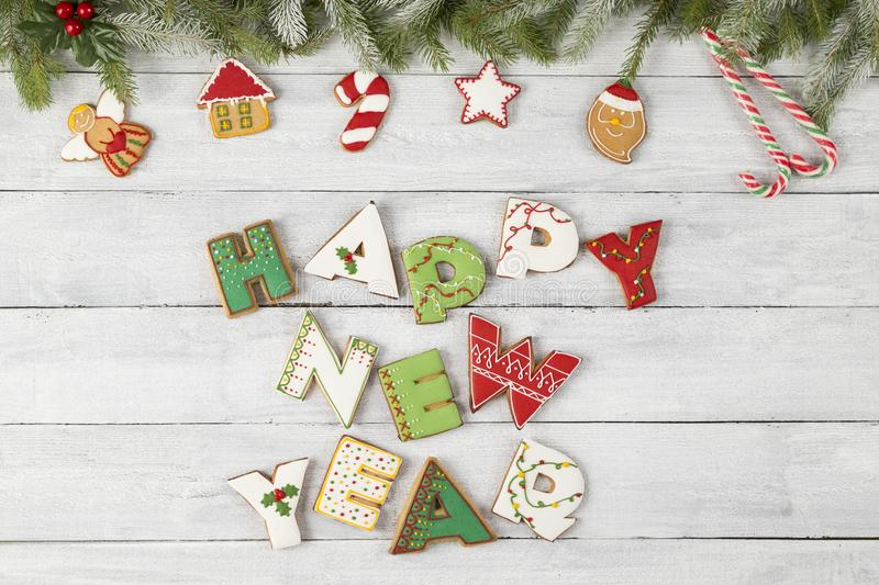 Happy New Year. Top view of nicely decorated colorful Christmas cookies shaped like letters Happy New Year on wooden background stock image