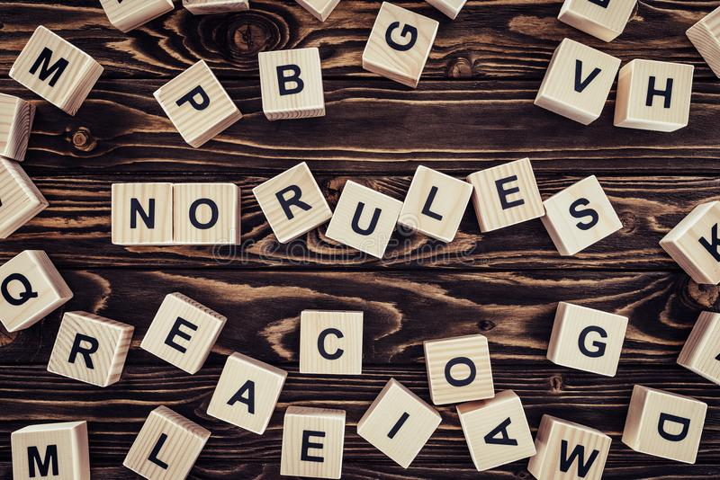 top view of no rules lettering made of wooden cubes on brown wooden tabletop stock photography