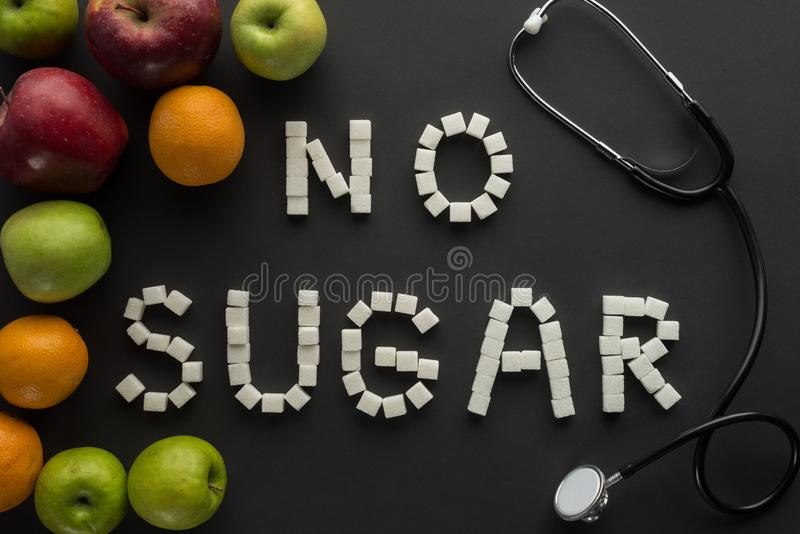 Top view of no sugar phrase made of sugar cubes with stethoscope and fruits. On black background stock photo