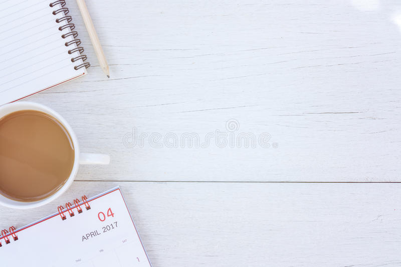 Top view note book, calendar and coffee cup on white wooden table royalty free stock image