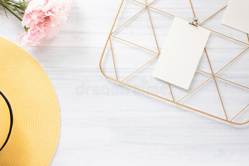 Top view note pad clip frame and summer yellow hat with pink flower on white wood table.summer vacation background stock image