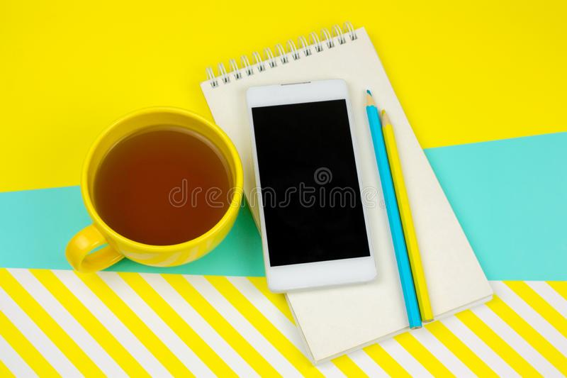 notebook with blank white paper sheet, smartphone,pencils and cup of tea royalty free stock image