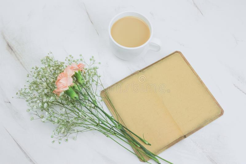 Notebook with empty vintage paper sheets ,coffee with milk cup and flowers. Top view notebook with empty vintage paper sheets ,coffee with milk cup and flowers royalty free stock photo