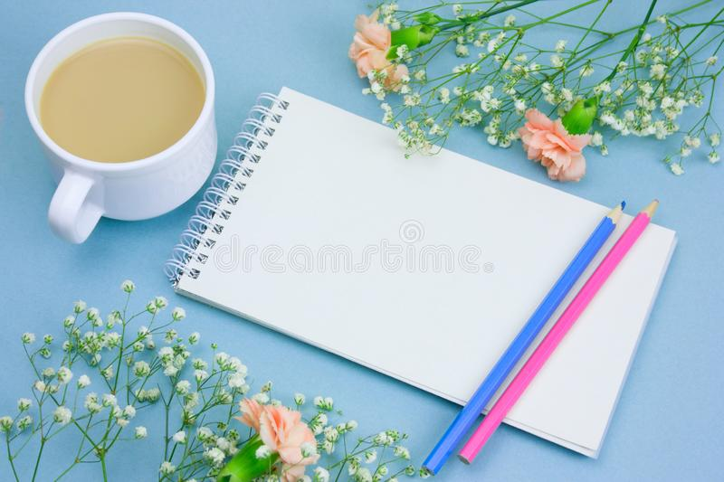 notebook with empty white paper sheet ,colored pencils,coffe with cream cup and floral frame on a pastel blue background stock photos