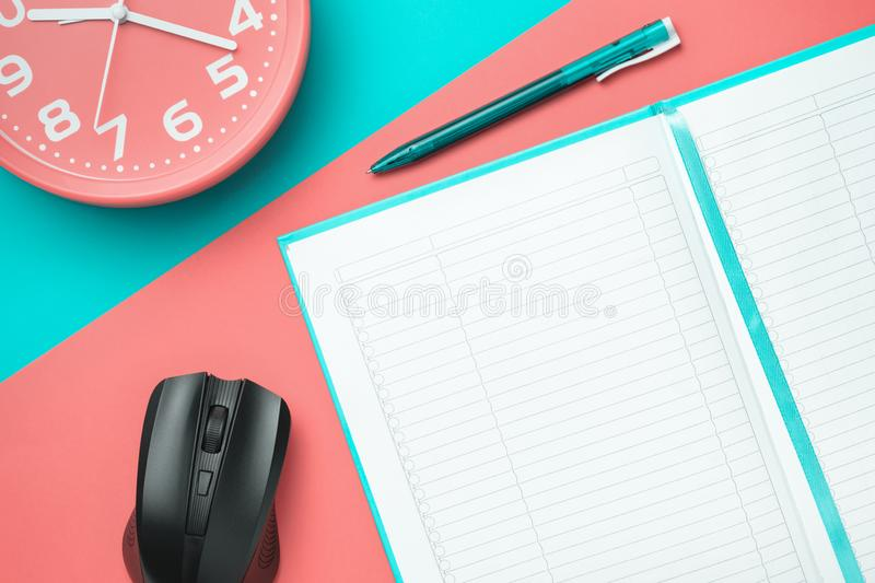 Top view notebook with a pen and a clock and a computer mouse on a colored background stock photography