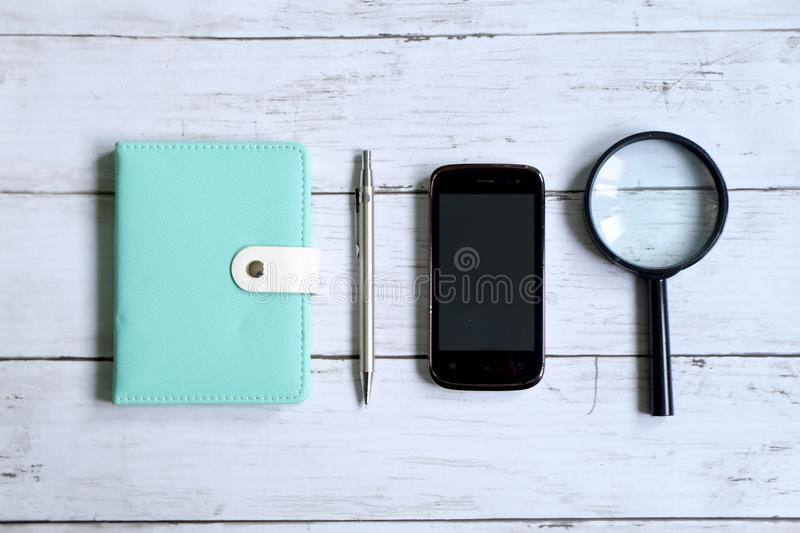 Top view of notebook,pen,smartphone and magnifying glass on white wooden background royalty free stock image