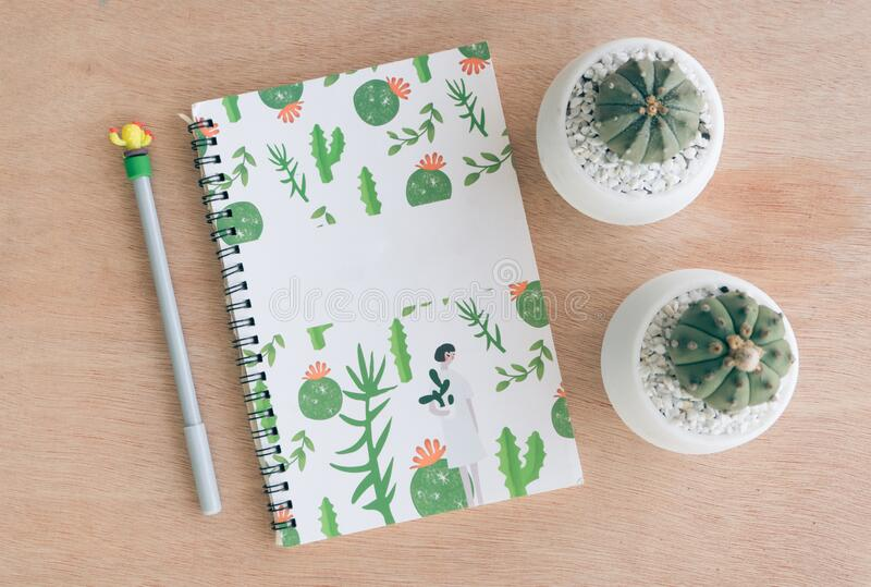 Top view of a Notebook Study and care cactus. On wood table in cactus cultivation house, Cactus nursery royalty free stock photo