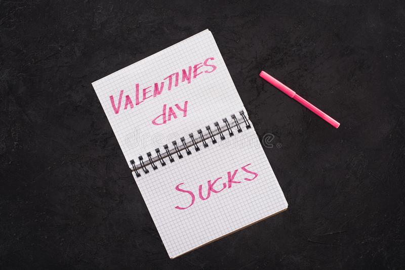 Top view of notebook with valentines day sucks and pen. On dark tabletop royalty free stock photos