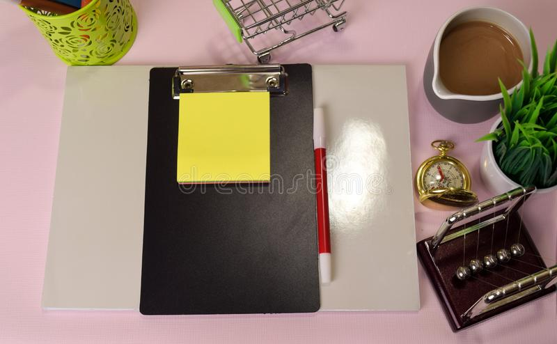 Top view of the notepad and clipboard with a marker drawing on a pink tabl. E, preparing to do homework. Drawing Working Desk Concept stock photo
