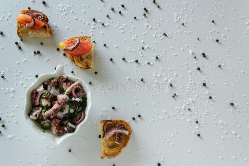 Top view of octopus salad with slices of toasted baguette - bruschetta on white background with black pepper and sea salt. stock images
