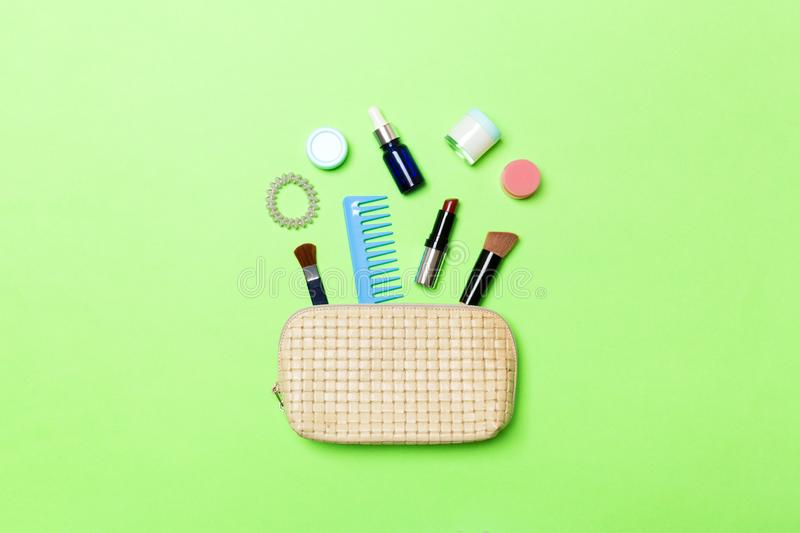 Top view od cosmetics bag with spilled out make up products on green background. Beauty concept with empty space for your design.  royalty free stock photos