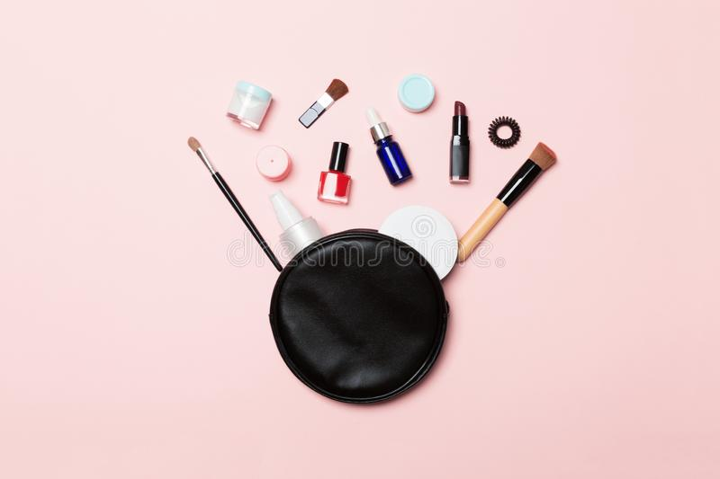 Top view od cosmetics bag with spilled out make up products on pink background. Beauty concept with empty space for your design.  royalty free stock photos