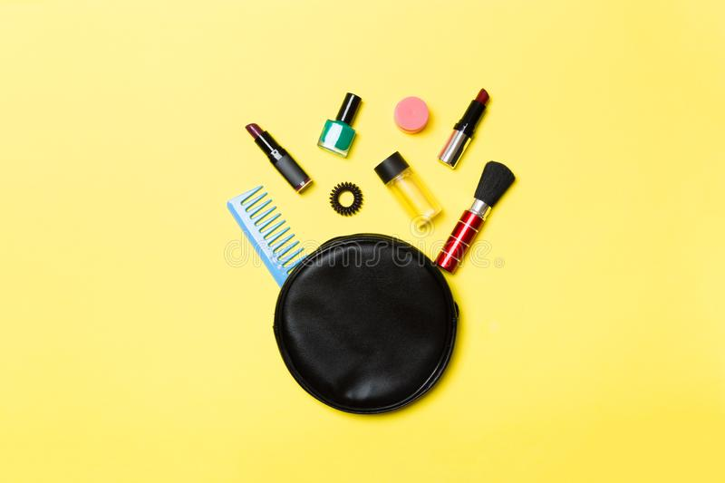 Top view od cosmetics bag with spilled out make up products on yellow background. Beauty concept with empty space for your design.  stock photography