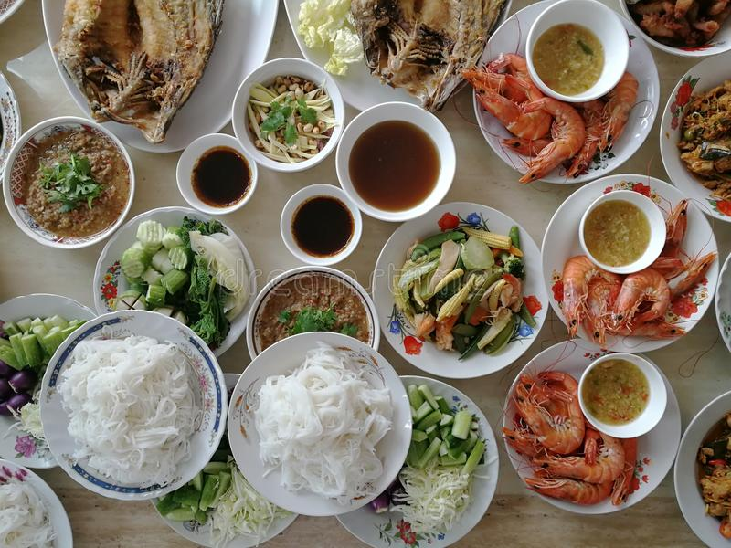 Top View of Offer food to the monk, Rice vermicelli with minced fishes and coconut milk in red curry , Barbecued shrimp , Stir Fr. Ied Vegetables and Fried Fish stock photography