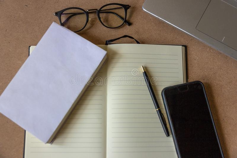 Top view of office desk with Blank white note book, eyesight glasses, mobile phone, pen and tablet on cork table background royalty free stock photography