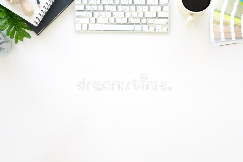 Top view office desk with designer table a Pantone, computer, co. Ffee and notebook paper sketch on white table artist workspace above view royalty free stock photo