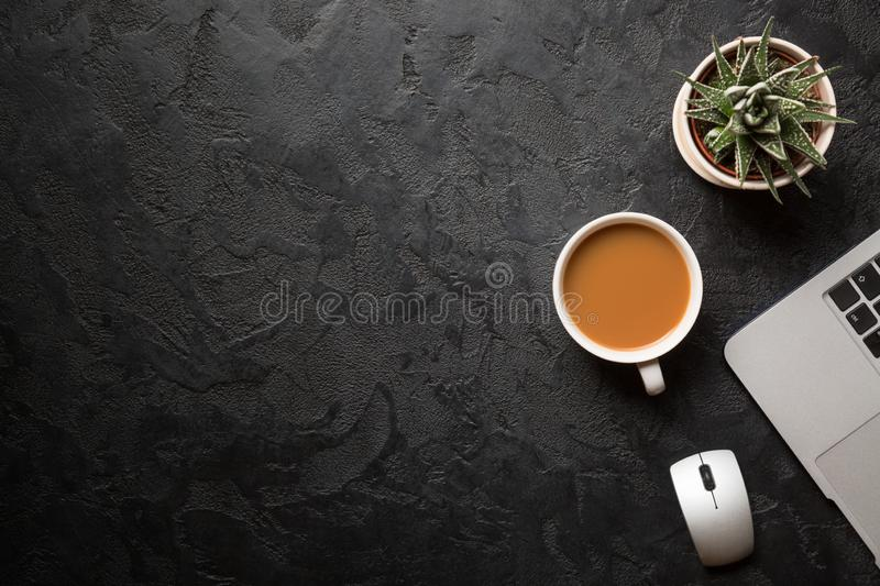 Top view of office desk. Green plant in a pot, cup of coffee, computer mouse and modern silver laptop on dark background. Copy royalty free stock image