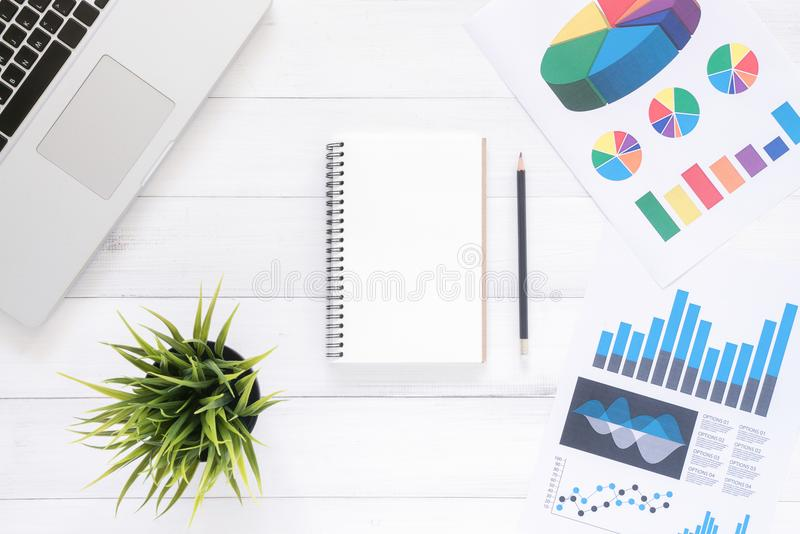 Top view office desk with laptop, mock up notebooks and plant on white wooden background. stock photo