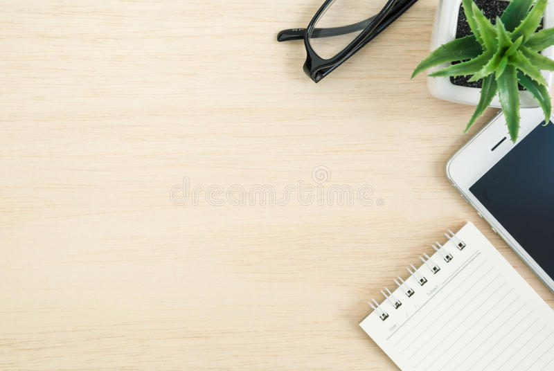 Top view of office desk with mobile phone and spiral notebook on stock images