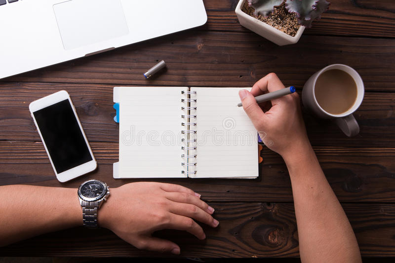 Top view office desk mockup: laptop, notebook, smartphone, pen, flower, and cup of coffee stock image