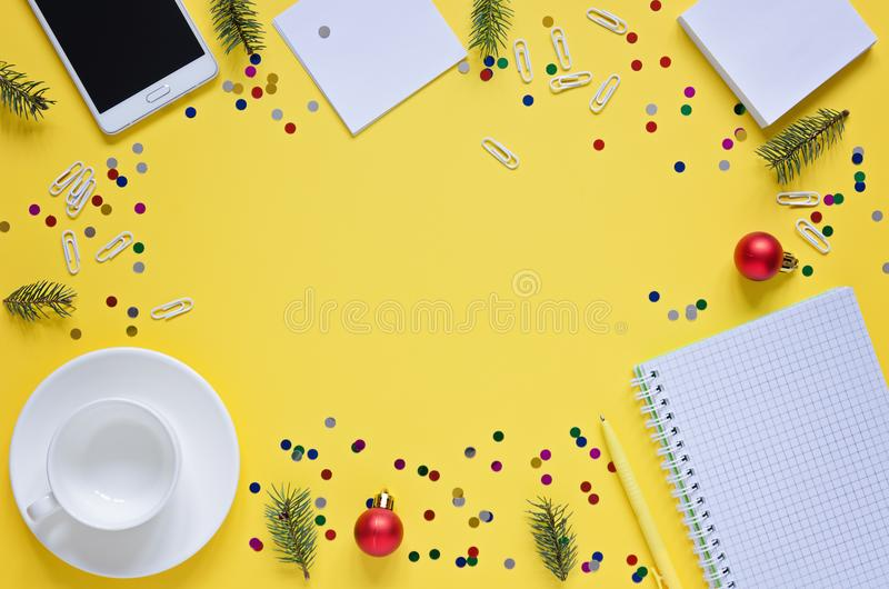 Top view office desk with notepads, phone, paper for notes, coffee cup, Christmas tree and toy on yellow background. stock photo