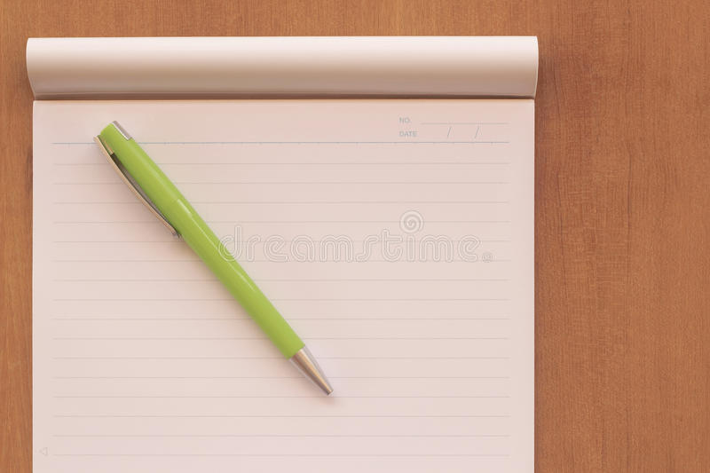 Top view of office desk with open spiral notebook, pen a green o stock image