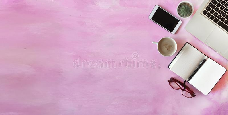 Top view of office desk on pink background stock photo